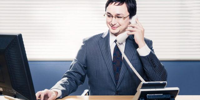電話をしながらPCを見る男性