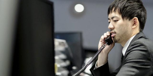 電話をしながら彼女宛てのメール返信に忙しい男性