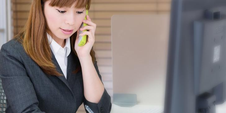 電話をしながらメモをする女性